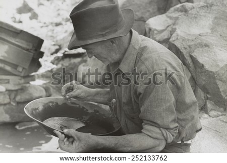 Man panning gold at Pinos Altos, New Mexico. He holds a gold nugget. May-June, 1940. Photo by Russell Lee. 13_236) - stock photo