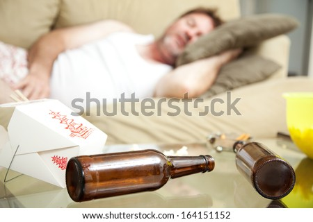 Man passed out on his couch in his underwear.  A full ashtray, empty beer bottles and empty Chinese take out container scattered on his coffee table.   - stock photo