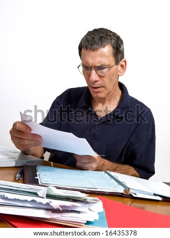 Man paying his monthly bills, looking shocked at a bill he just opened. - stock photo