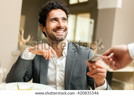 Man paying the bill with a credit card - stock photo