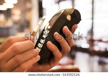 Man paying with NFC technology on credit card, in restaurant, bar, cafe - stock photo