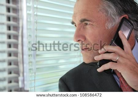 Man peering through some blinds - stock photo