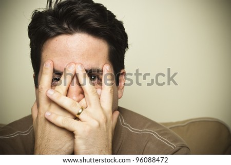 Man peers through his fingers. - stock photo
