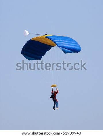 Man pending from a blue and yellow parachute