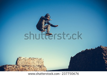 man performs freerunning jump on stones - stock photo
