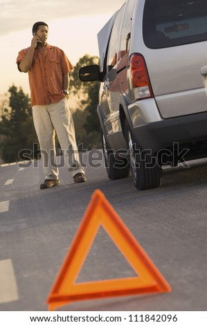 Man phoning with warning triangle in foreground
