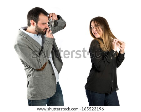 Man photographing a girl over white background