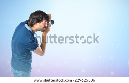 Man photographing over blue background