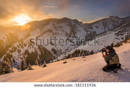 Man photographing the sunset in the mountains, in Romania - stock photo