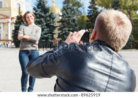 Man photographing young beautiful woman against city`s attractions. Summer time, outdoors. Loving couple - stock photo