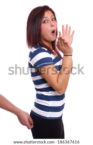 man pinching a young woman's bottom from behind - stock photo