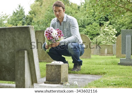 Man Placing Flowers By Headstone In Cemetery - stock photo