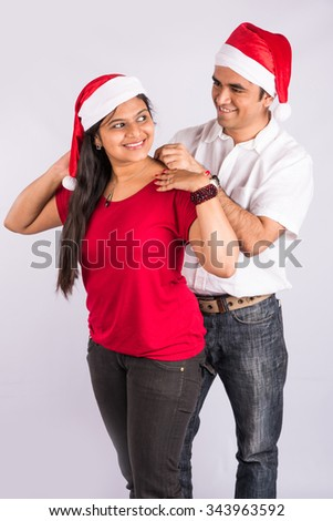 Man placing necklace on woman's neck in christmas time, indian man gifting necklace to wife of girlfriend on christmas, asian couple and gifting necklace, isolated on white background, standing pose  - stock photo