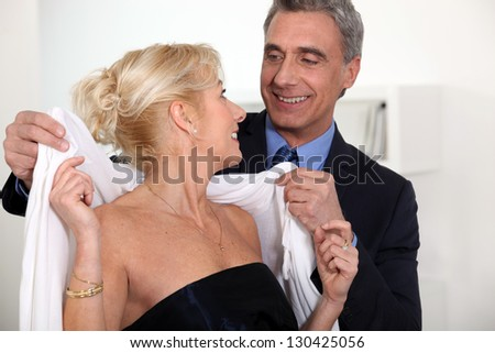 man placing scarf on woman - stock photo