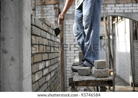 Man plastering and layering wall bricks in shallow depth of field. - stock photo