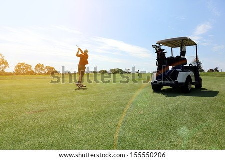 Man playing a game of golf by his cart - stock photo