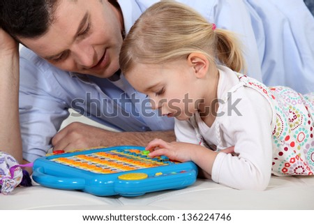Man playing a toy computer with a little girl - stock photo