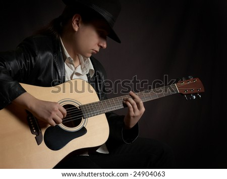 Man playing acoustic guitar at rock concert