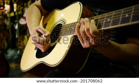 Man playing acoustic guitar in music store - stock photo