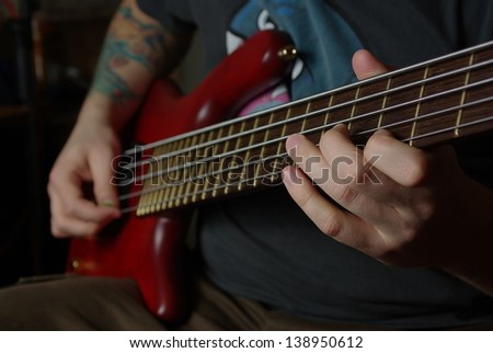Man playing an bass guitar with brown neck - stock photo