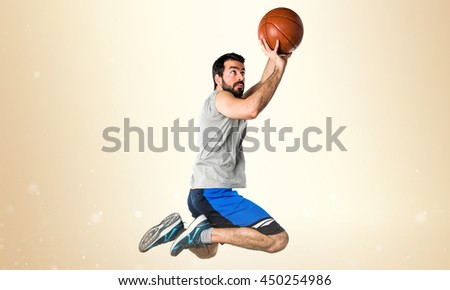 Man playing basketball jumping over ocher background
