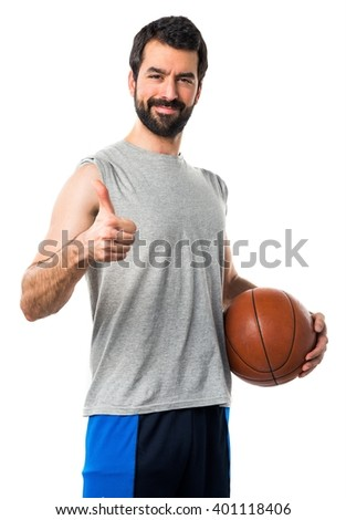 Man playing basketball with thumb up