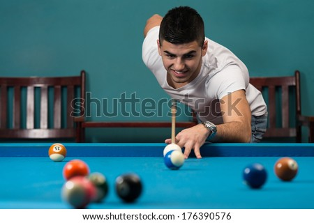 Man Playing Billiards - Young Man Lining To Hit Ball On Pool Table - stock photo