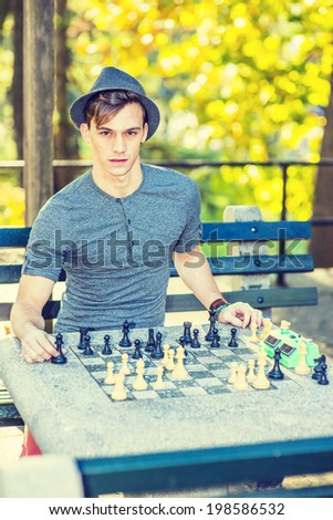 Man Playing Chess. Dressing in a gray long sleeves with roll-tab Henley shirt, wearing a woolen Fedora hat, a young handsome guy is playing chess outside in golden autumn afternoon. Ready to Play  - stock photo