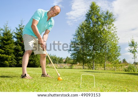 Man playing croquet on cottage - stock photo