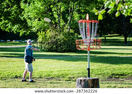man playing disc golf in a park on a summer day - stock photo