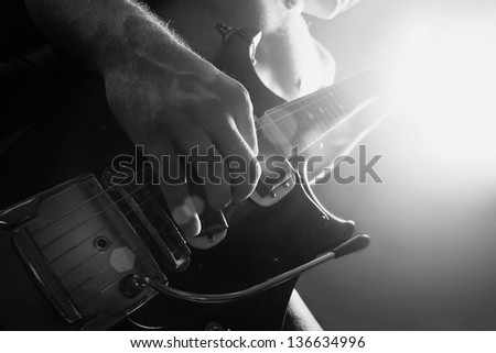 man playing electrical guitar in black and white