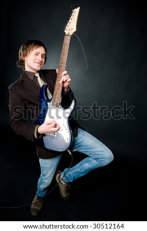 Man playing electro guitar over black background - stock photo
