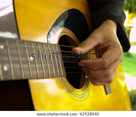 man playing folk guitar with left hand - stock photo