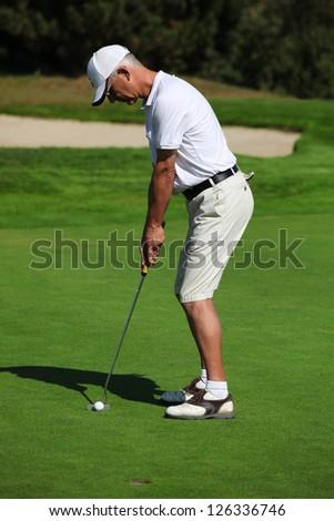 Man playing golf - stock photo