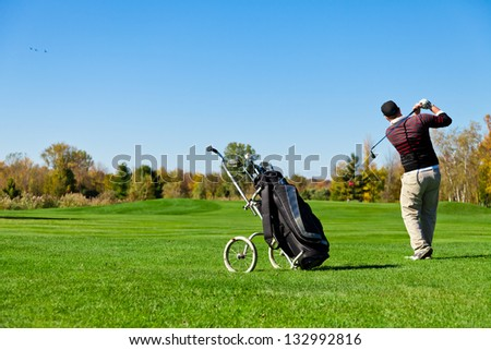 Man playing golf on a beautiful day - stock photo