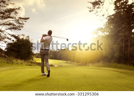 Man playing golf on a golf course in the sun - stock photo