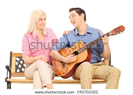 Man playing guitar for a girl seated on bench isolated on white background - stock photo