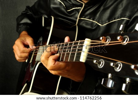 Man playing guitar on black background - stock photo