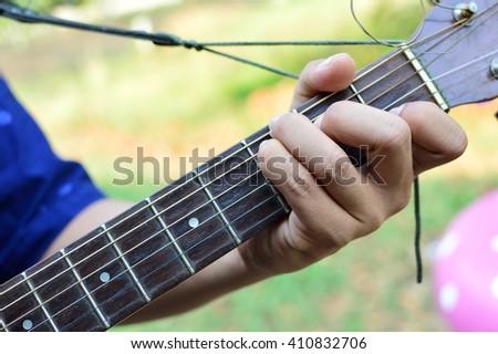 man playing guitar on C chord - stock photo