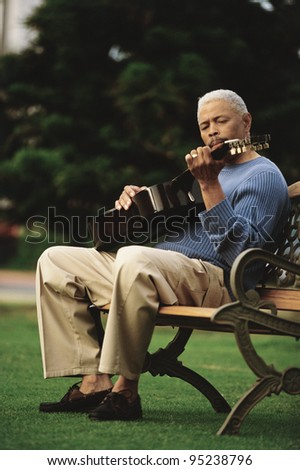 Man playing guitar on park bench - stock photo