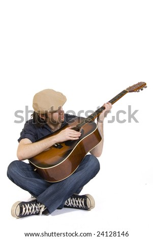 man playing his acoustic guitar seated - stock photo