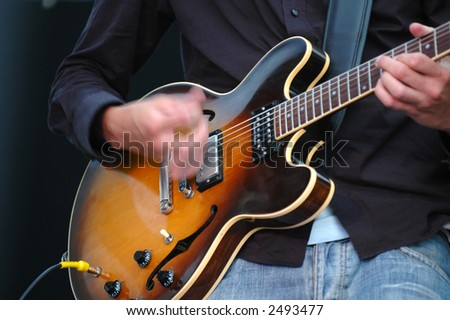 Man playing his guitar. Note his hand is in motion.