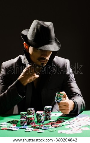 Man playing in dark casino - stock photo