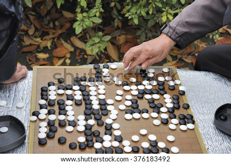 Man playing in the outside Baduka that is the Korean name for Go - stock photo