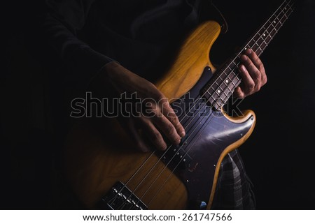 Man playing on bass guitar - stock photo