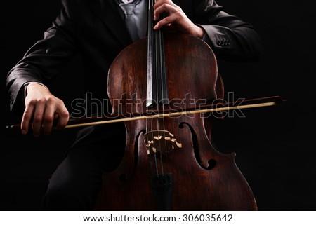 Man playing on cello on dark background - stock photo