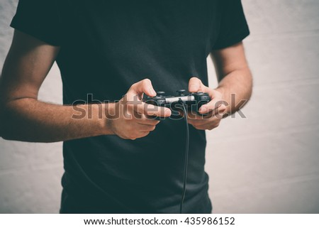 Man playing on the joystick in a game console - stock photo