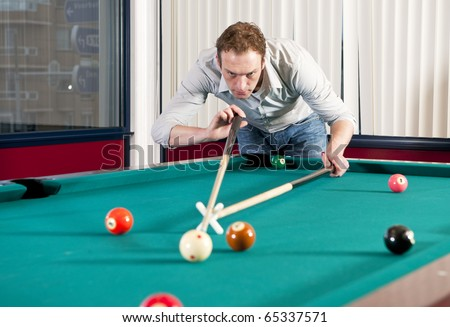 Man, playing pool and using a mechanical bridge to reach the cue ball