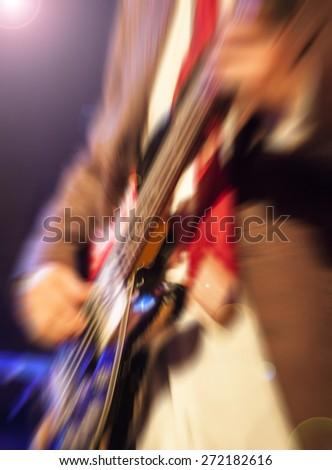 man playing rock guitar on concert,blurred rock background - stock photo
