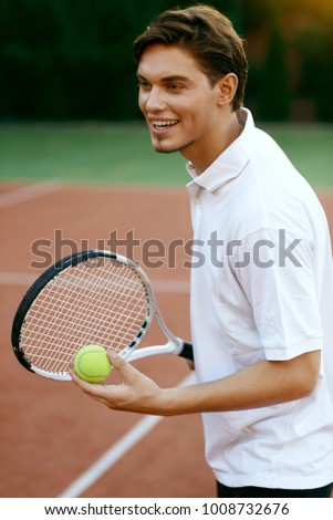 Man Playing Tennis Outdoors. Portrait Of Handsome Tennis Player With Racket And Ball On Open Court During Sport Game. Leisure Activity. High Quality Image.